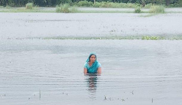 Monsun-Überschwemmungen verstärken die Corona-Folgen. Hier: Frau in Fluten