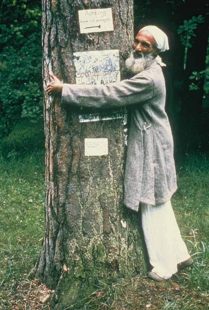 Sunderlal umarmt im Stile der Chipkobewegung einen Baum
